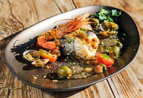 Dorada rellena de mató y verduras con gambas, almejas,olivas y alcaparras
